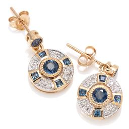 Sale 9160 - Lot 388 - A PAIR OF DECO STYLE SAPPHIRE AND DIAMOND EARRINGS; each an 11mm round disc centring a round cut sapphire surrounded by 4 carre cut...