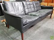 Sale 8493 - Lot 1012 - Kurt Østervig Black Leather Three-Seater Lounge over Turned Teak Legs