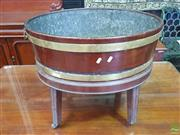 Sale 8617 - Lot 1075 - George III Mahogany Open Cellarette or Wine Cooler, the cellarette of oval barrel shape with brass bands & handles, having the origi...