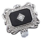 Sale 9037 - Lot 387 - AN EDWARDIAN STYLE DIAMOND AND ONYX RING; octagonal mount with scroll surround set with an onyx plaque inset with a round brilliant...