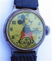 Sale 8387A - Lot 23 - A rare 1933 Mickey Mouse wristwatch by Ingersoll USA. Last serviced 2011. Running fine. Original finish on case and dial. 32 mm.