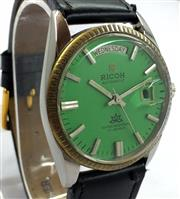 Sale 8387A - Lot 39 - A vintage mens Ricoh automatic wristwatch with day / date window. Green dial. Stainless steel case with leather band. 37 mm. Runnin...