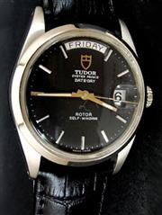 Sale 8387A - Lot 40 - A fine vintage mens Tudor by Rolex day / date wristwatch. Stainless steel case with black dial. 35.5 mm. Rolex crown and case. Full...