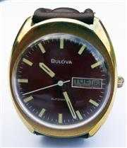 Sale 8387A - Lot 41 - A vintage mens Bulova red dial day / date wristwatch. Rolled gold plated case. Automatic. Running condition. 37 x 34 mm.