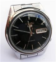 Sale 8387A - Lot 42 - A vintage mens Seiko 5 all stainless steel automatic wristwatch. Black dial with day / date. Running condition. 35 mm.