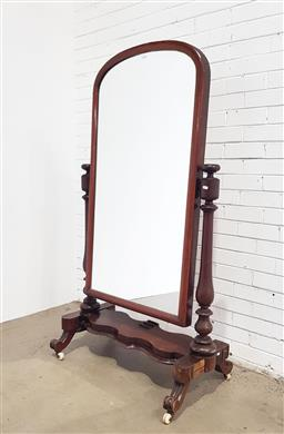 Sale 9142 - Lot 1001 - Victorian Mahogany Cheval Mirror, with arched top & turned supports, on a shaped base with outswept feet - veneer losses, wheel in t...