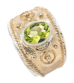 Sale 9213 - Lot 315 - A TWO TONE SILVER PERIDOT RING; collet set with an oval cut peridot of approx. 1.24ct to decorative tapered band, width 15mm, size J...