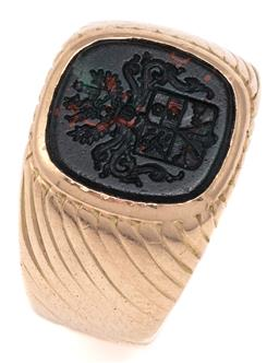 Sale 9115 - Lot 376 - A VINTAGE 14CT GOLD HARD STONE SEAL SIGNET RING; centring a cushion shape bloodstone intaglio featuring coat of arms with dragons, f...
