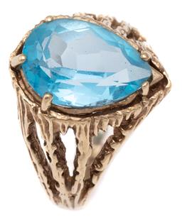 Sale 9115 - Lot 317 - A RETRO 9CT GOLD TOPAZ COCKTAIL RING; featuring a pear cut blue topaz of approx. 6.30ct to textured organic shoulders, size P, width...
