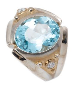 Sale 9213 - Lot 313 - A TWO TONE SILVER TOPAZ RING; rub set with an oval cut blue topaz of approx. 5.48ct to gilt top set with 2 round cut zirconias to ta...