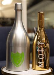 Sale 8709 - Lot 1025 - A Moet bottle flask in gilt together with a brushed aluminium Dom Perignon example, height of taller 51cm