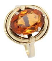 Sale 9083 - Lot 307 - A VINTAGE 14CT GOLD CITRINE RING; centring an approx. 4ct oval cut citrine on a swirl surround, size K, top 17 x 15mm, wt. 6.91g.