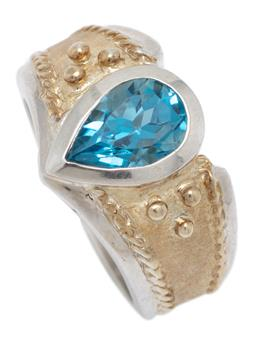 Sale 9213 - Lot 362 - A SILVER BLUE TOPAZ RING; 12mm wide ring with decorative gilt top rub set with a pear cut blue topaz of approx. 1.50ct, size N, wt....