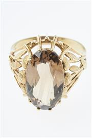 Sale 8293 - Lot 306 - A 14CT GOLD STONE SET RING; centring an oval smoky quartz to foliate shoulders, size P, wt. 5.6g.