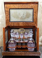 Sale 8703A - Lot 33 - A walnut and five panelled etched glass tantalus containing four decanters in amethyst  and seven liqueur glasses, H x 26cm