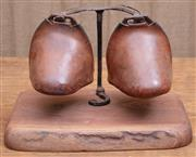 Sale 8984H - Lot 100 - A pair of Eastern cupped leather stirrups mounted over a timber base bearing a Wombat Hollow plaque. Width 40cm