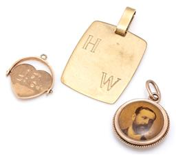 Sale 9115 - Lot 309 - THREE GOLD PENDANTS; a 9ct spinning heart, length 16mm, 2 in 8ct gold, a souvenir portrait locket, length 24mm, and a plaque inscrib...