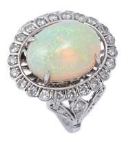 Sale 8982 - Lot 397 - AN 18CT WHITE GOLD OPAL AND DIAMOND COCKTAIL RING; featuring an oval cabochon Ethiopian opal of 5.20ct (13.9 x 10.7mm) to halo surro...