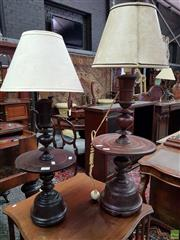 Sale 8576 - Lot 1009 - Two Possibly Burmese Turned Timber Table Lamps, of graduated size with central discs, each with a cream shade