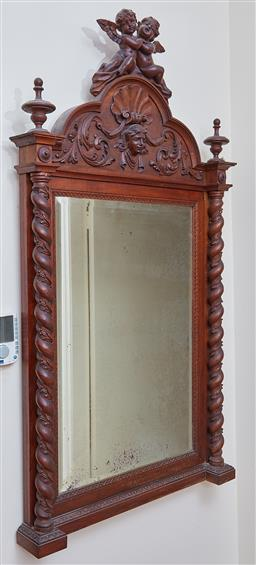 Sale 9103M - Lot 499 - A bevelled edge over mantle mirror with carved timber frame with cherubic surmount, 150cm x 85cm