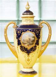 Sale 9066H - Lot 30 - A twin handled Coalport vase with a castle painted cartouche, with cobalt blue detail on a pale lemon ground and gilding. H 26cm.