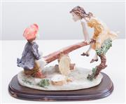 Sale 8369A - Lot 96 - A bisque porcelain figural group of a boy and girl frolicking on a see-saw on timber base, L 28cm