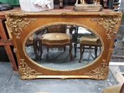 Sale 8925 - Lot 1046 - An oval bevel edged mirror in an ornate gilt frame
