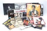Sale 8733 - Lot 14 - Ali Calendars. Eleven calendars, 8 other books including Big Fight by Frank Butler (Clay v Liston) and 6 DVDs on Ali.