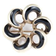 Sale 8866 - Lot 320 - A NORWEGIAN STERLING SILVER ENAMELLED BROOCH; floral design, each tapered hoop inlaid with black enamel, width 44mm.