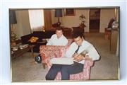 Sale 8733 - Lot 28 - Two large framed photographs of Ali, including showing Ali signing Warrens scrapbook (no glass).