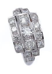 Sale 9080J - Lot 57 - An 18ct white gold and 17 diamond ring. The centre panel set with 3 diamonds, flanked by 2 rectangular panels,each set with 4 diamon...