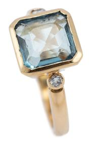 Sale 9066 - Lot 338 - AN 18CT GOLD AQUAMARINE AND DIAMOND RING; rub set with an approx. 1.70ct square emerald cut aquamarine between shoulders each set wi...