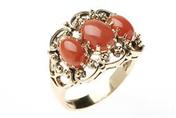 Sale 9213 - Lot 339 - A NOUVEAU STYLE CORAL RING; set in a 9ct gold scrolling mount with 3 oval cabochon corals, size O, top 14 x 18mm, wt. 4.3g.