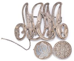Sale 9124 - Lot 379 - TWO ANTIQUE SILVER BROOCHES; one composed of 2 George II shillings (1787 &1743), and Victorian 57 x 75mm engraved cut out monogram,...