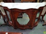 Sale 8559 - Lot 1039 - Victorian Carved & Figured Walnut Credenza, with white serpentine marble top, above an oval & two arched panel mirror doors