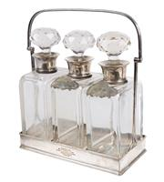 Sale 8439A - Lot 41 - An antique three bottled tantalus, each with HMSS collars, and two spirit labels in silver plate gallery, inscription to front dated...