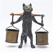 Sale 9080W - Lot 10 - A continental bronze painted cat bearing a yoke suspending buckets for vestas (matches) with rough strike area to base. Height 11cm