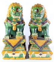 Sale 8972 - Lot 19 - Pair of large Sancai glazed Buddhist lions seated on stepped pedestals (H61cm)