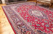 Sale 8435A - Lot 15 - A Persian wool carpet with blue medallion arabesque on claret ground, 210 x 315cm