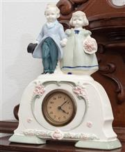 Sale 9070H - Lot 25 - A porcelain clock and key the top adorned with formally addressed with angelic children, Height 14cm