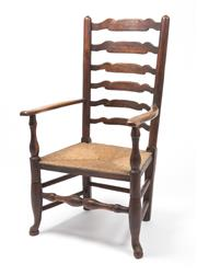 Sale 8518A - Lot 48 - An antique Georgian dark Irish oak ladder back armchair. The turned highback uprights with 6 shaped ladder rails above a rush seat....