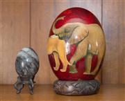 Sale 8313A - Lot 80 - A South African ostrich egg hand painted by F Kondowe with safari animals on a wooden stand total height 18cm, together with a marbl...