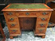 Sale 8666 - Lot 1019 - Georgian Style Walnut Knee-Hole Desk, the burr veneered top with tooled green leather inlay, having nine marquetry drawers flanking...