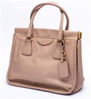 Sale 8921 - Lot 12 - A PRADA NUDE SAFFIANO LEATHER BORSA CERNIERA BAG; with tag, rolled handles, snap top closure and gold tone hardware and mirror, 33 x...