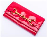 Sale 8921 - Lot 13 - A GUCCI PATENT LEATHER HORSEBIT CONTINENTAL WALLET; hot pink patent leather and gold tone metal exterior and leather and suede inter...