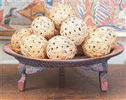 Sale 8550H - Lot 23 - An Asian red lacquered raised tray with tripod feet containing woven cane balls, D 45cm
