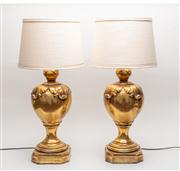 Sale 8716A - Lot 31 - A pair of  large gilt lamps, the balloon shaped body decorated with four boldly moulded leaves to the top, the circular stepped foot...