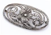 Sale 9015J - Lot 81 - A vintage sterling silver and marcasite brooch C: 1940s, the scroll pierced oval panel centered by a flower L: 60mm