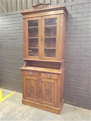 Sale 9048 - Lot 1055 - Edwardian Oak Bookcase, with two glass panel doors above an alcove, with two drawers & two carved panel doors below