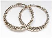 Sale 8517A - Lot 91 - A pair of Thai hilltribe white metal coiled bangles, D 7.5cm